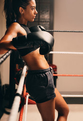 Young female boxer leaning on ropes