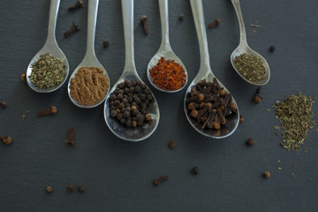In de dag Kruiden herbs and spices selection, spoons with spices on black background: paprika, black pepper, red pepper, peppermint, clove