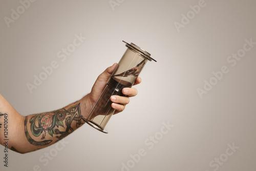 e2b3ac30a Closeup of tattooed man's hand holding aeropress