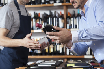 Midsection Of Customer Showing Wine Bottle To Salesman