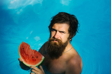 man with watermelon in pool