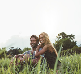 Loving couple sitting on grass field