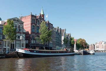 Houses and barges on the river Amstel in Amsterdam