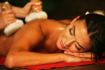 Young woman lying on wooden spa bed. Poultice hot herbal massage in spa salon.