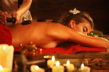 Woman lying on wooden spa bed. Lastone therapy massage in spa salon. Girl on burning candles background in massage spa salon.