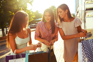 Beautiful girl with packages after shopping A picture of a group of happy friends shopping in the city. Girl walking around the city after shopping. good mood. Evening light. shopping concept