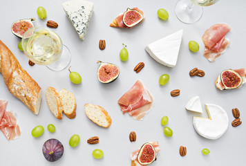 wine and snacks on grey table