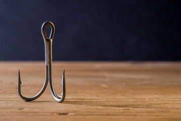 Fish Hook on a wooden surface with dark background