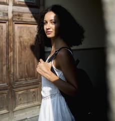 Portrait of young woman standing in front of wooden door
