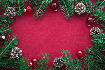 Frame with xmas tree and ornaments on red canvas background. Merry christmas card. Winter holiday theme. Space for text. Happy New Year.