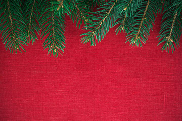 Frame with xmas tree on red canvas background. Merry christmas card. Winter holiday theme. Space for text. Happy New Year.