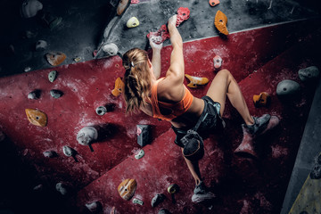 Female climbing on an indoor climbing wall.