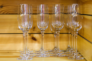 Empty glasses for champagne on the wooden shelf.