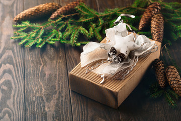 Christmas gift in a beautiful and elegant box with fir branches and cones on the rustic wooden table. Vintage style