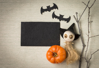 Halloween concept, black card with ghost doll and pumpkin