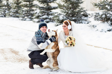 Wedding couple and a cute dog in winter time