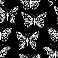 Seamless pattern with beautiful butterflies created from abstract floral tracery on a black background
