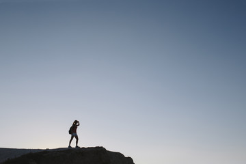 silhouette young woman tourist with backpack standing on cliff