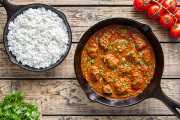 Beef Madras curry slow cook Indian spicy garam masala lamb food in cast iron pan on vintage wooden table background. Traditional India culture restaurant dish.