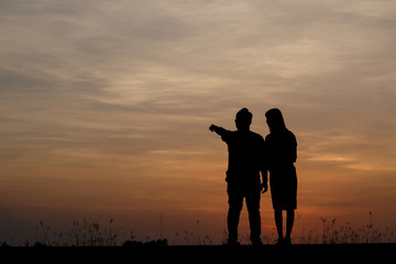 Silhouette man and woman with beautiful the sky at sunset..Backg