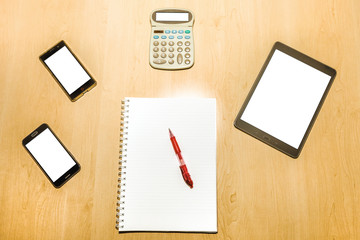Flat lay of an office desktop wooden table with mobile phones, tablet pad, calculator and a notepad with red pen. Blank screens and paper for copy space