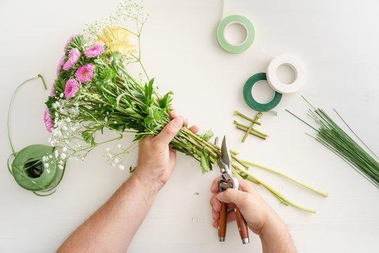 Man arranging flowers to make a bouquet
