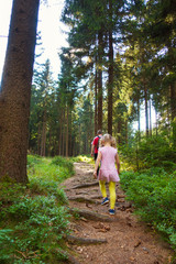 Little daughter with her father hiking in forest