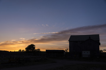 Barn silhouetted by sunset