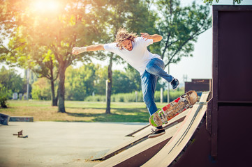 Young man riding skate at park and falling down