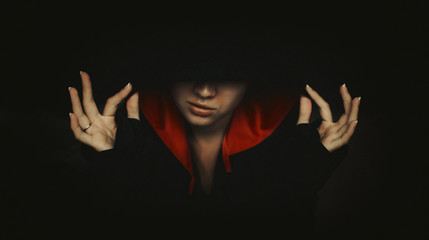 Portrait of mysterious woman in dark hood