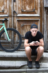Young boy using cell on doorstep with bike