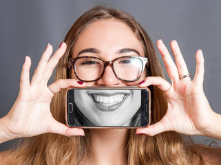 girl with smartphone that you take a picture to your smile