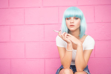 Sexy young girl in modern futuristic style with blue wig and cigarette crouching and looking into the camera over pink wall background