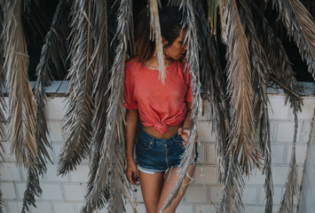 Brunette woman posing in dry palm leaves