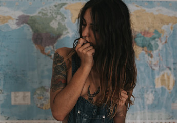 Sexual brunette woman in denim cloth posing on world map background