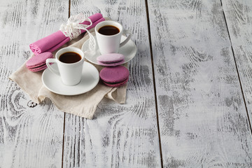 Two cups of freshly brewed espresso coffee with macaroons on a textured wooden table top with copyspace