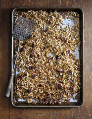 Overhead view of granola in tray on wooden table