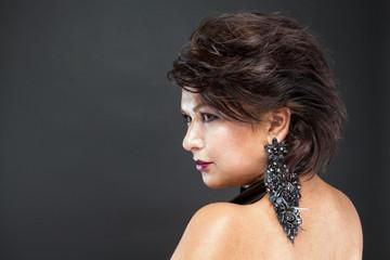 Профиль женщины с красиво уложенными волосами и шикарными черными серьгами.