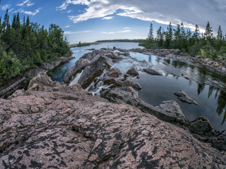 extreme wide angle shot of river draining into lake, quartz rock in foreground