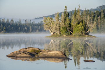 partially submerged rocks in calm lake at sunrise, with lake mist and forest in background