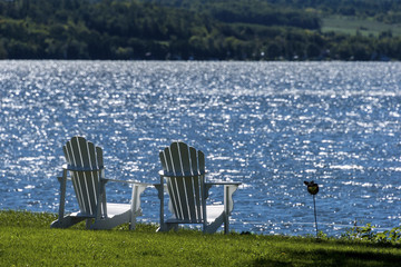 wooden cottage chairs facing sparkling lake