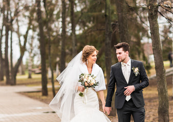 Bride and groom walking in the autumn or winter park