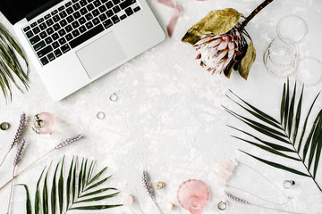 flat lay feminine home office workspace with laptop, proteus flower, necklace, palm branches and accessories. top view