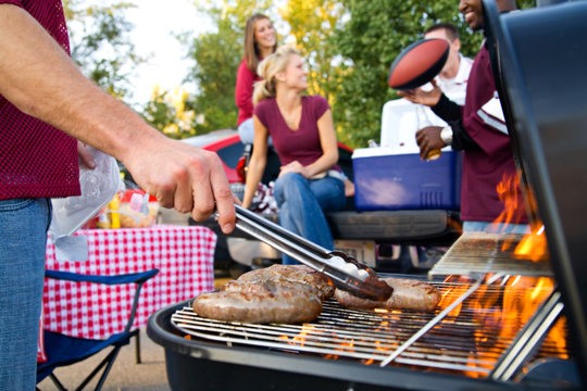 Tailgating: Bratwurst or Sausage On The Grill At Tailgate Party
