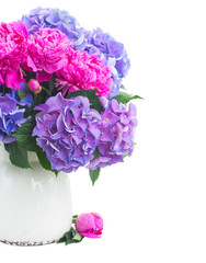 Bright pink peony, eustoma and blue hortensia fresh flowers bunch in vase close up isolated on white background