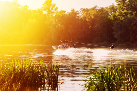 boat pulls man water skiing on the river. Sunset. Splashes of water.