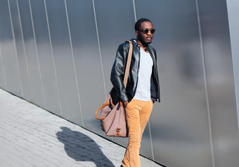 Wall Mural - Fashion african man walks in evening city over urban background