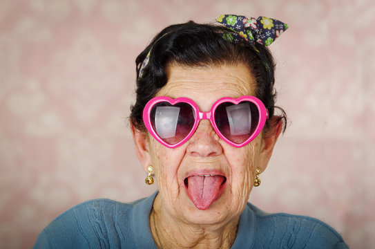 Older cool hispanic woman wearing blue sweater, flower pattern bow on head and pink heartshaped sunglasses looking into camera showing her tongue