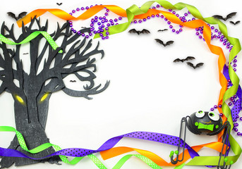Halloween border of a rough textured wooden cutout of bare tree shape painted black. A silly spider, bats and purple, green and orange ribbons and beads frame the copy space on white background