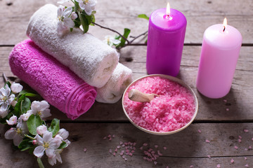 Spa or wellness setting. Sea salt in bowl, towels, candles and